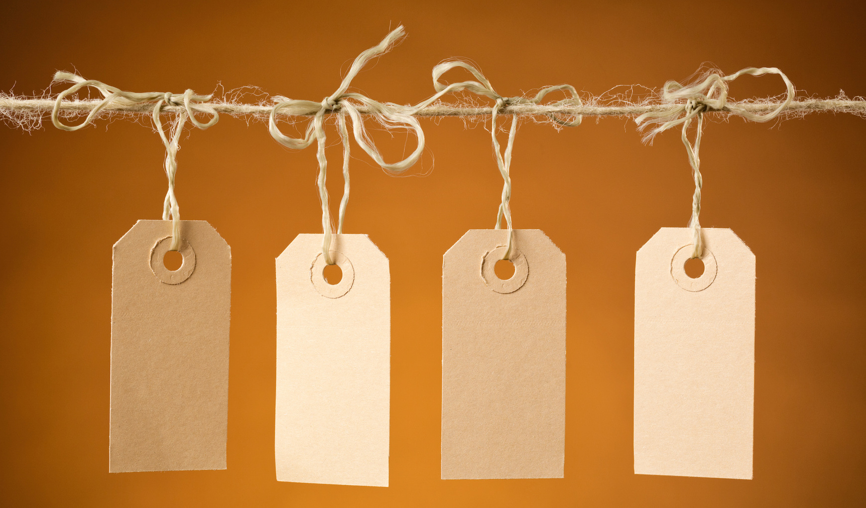 Four blank paper price tag labels hanging next to each other on a rope with orange background.
