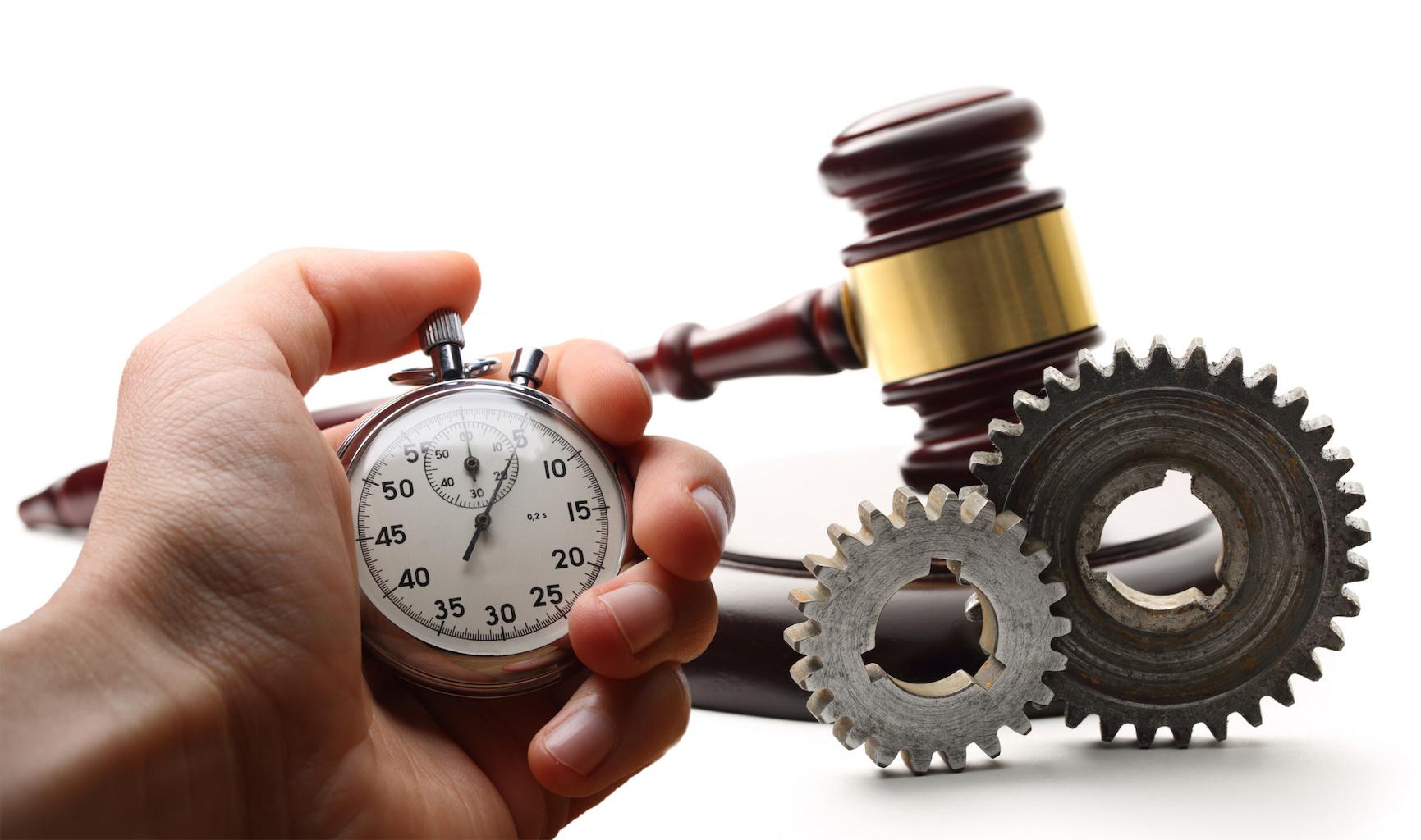 Steel cogwheels, wooden gavel and stopwatch in hand